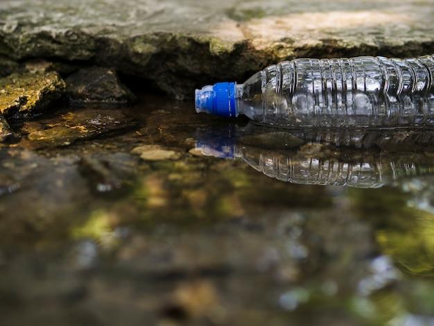 Transparante lege plastic waterfles die op water drijft