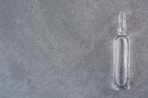 Transparante medische ampul op marmeren tafel.