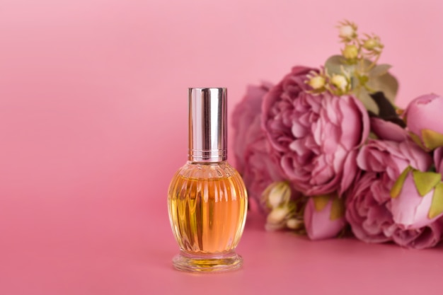 Transparante parfumfles met boeket van pioenrozen op roze achtergrond. aromatische essentiefles