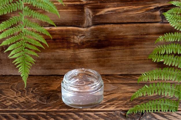 Transparante pot vochtinbrengende gelcrème op een houten bord met varenbladeren. spa natuurlijk biologisch schoonheidsproduct verpakkingsontwerp.