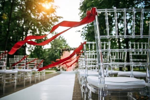 Transparante stijlvolle stoelen versierd met rode linten voor de huwelijksceremonie buiten. rijen stoelen in het park, abstracte achtergrond.