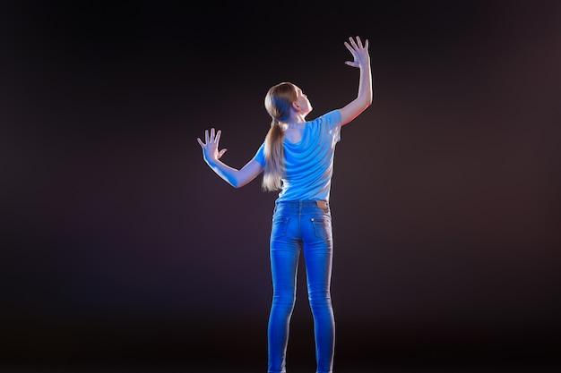 Transparante technologie. leuke aantrekkelijke vrouw die voor het virtuele paneel staat terwijl ze haar handen ertegen drukt