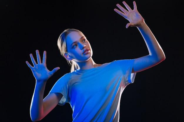 Transparante technologie. mooie blonde vrouw stond voor het sensorische scherm terwijl ze naar haar handen keek