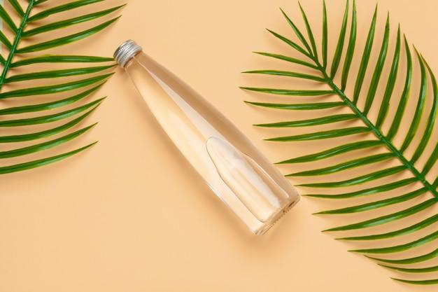 Transparante vloeibare fles met tropische palmbladen