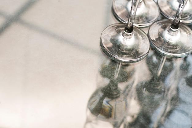 Transparante wijnglazen op reflecterende achtergrond