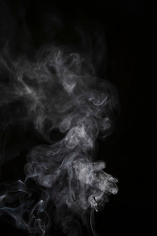 Transparante witte rookbeweging tegen zwarte achtergrond