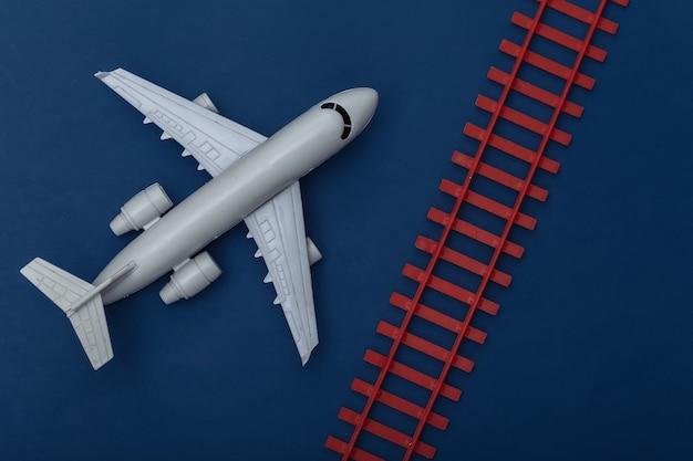 Transport en logistiek, reisconcept. stuk speelgoed vliegtuig, spoorweg op een klassieke blauwe achtergrond