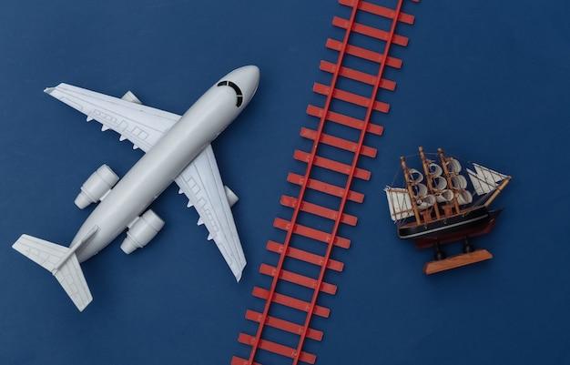 Transport en logistiek, reisconcept. stuk speelgoed vliegtuig, spoorweg, schip op een klassieke blauwe achtergrond