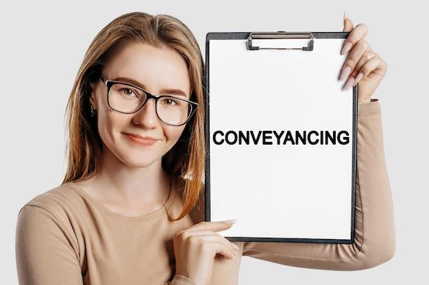 Transporteren. mooie jonge zakenvrouw met een bril houdt een klembord vast met mock-up ruimte geïsoleerd op een grijze achtergrond