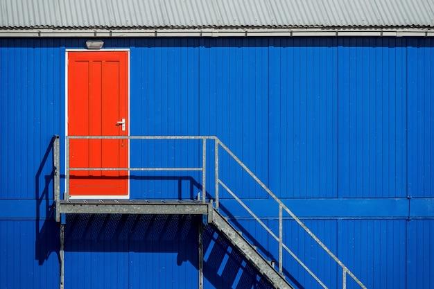 Trap bij de blauwe muur van een garage die naar de rode deur leidt
