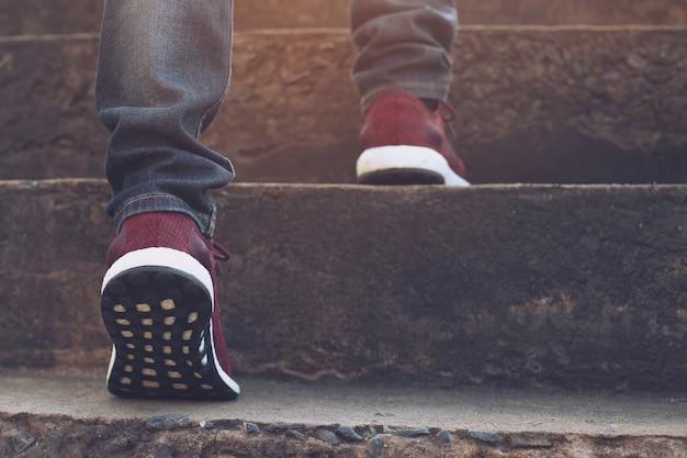 Trap. close-up benen jeans en schoenen sneakers rood van jonge hipster man een persoon lopen intensivering de trap op in de moderne stad, ga de trap op, succes, groei op. zonneschijn in de ochtend.