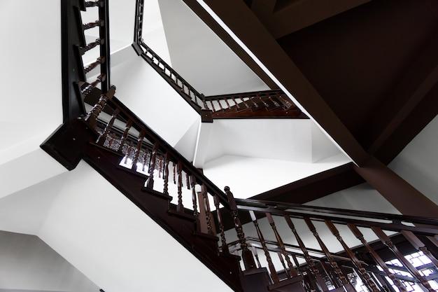 Trap en glanzende houten vloer van mooi aantrekkelijk luxehuis met witte muren met rond venster bovenop
