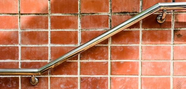 Trap met een metaalleuning bij oude bakstenen muur