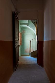 Trap van een oud huis gezien vanuit de duisternis van een gang