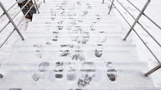 Trapleuningen en sneeuw. gladde treden, ijs bedekt met voetafdrukken, horizontaal schot buiten.