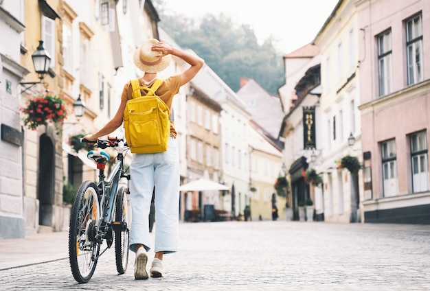 Travel europe jong meisje met rugzak en stadsfiets in oude straat in het centrum van ljubljana