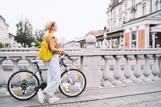 Travel europe jong meisje met stadsfiets op triple bridge in het oude centrum van ljubljana