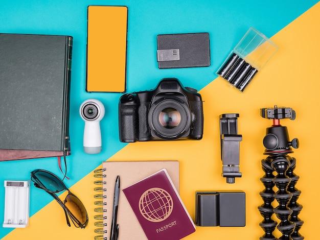 Traveler blogger kit voor zomervakantie. bovenaanzicht. plat leggen. camera met accessoires naast zonnebril, boeken, smartphone, papieren notitieboekje en paspoort