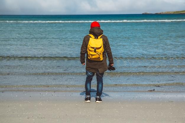 Traveler is een professionele fotograaf die op een zandstrand op de achtergrond van de zee staat