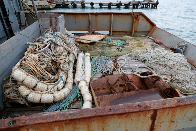 Trawl, pelagische planken, visnet ligt op het visserijdek van een kleine vissersboot