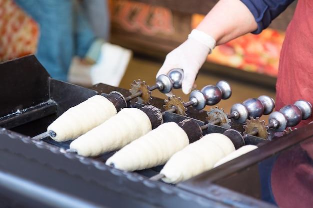 Trdelnik voorbereiden. traditioneel tsjechisch heet zoet gebak dat wordt verkocht in de straten van praag en andere steden in tsjechië.
