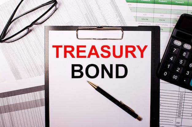 Treasury bonds is geschreven op een wit vel papier, naast de bril en de rekenmachine
