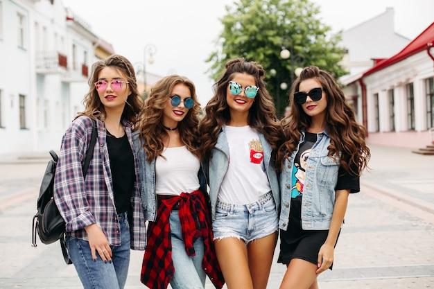 Tredny glimlachende vriendinnen lopen over de straat met de enige man.