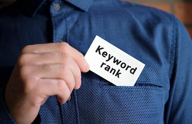 Trefwoorden rang - tekst op een wit bord in de hand van een man in overhemd