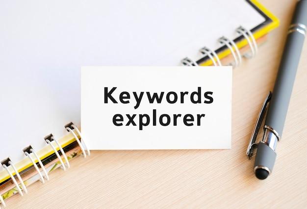 Trefwoorden verkenner - tekst op een notitieboekje met een veer en een grijze pen