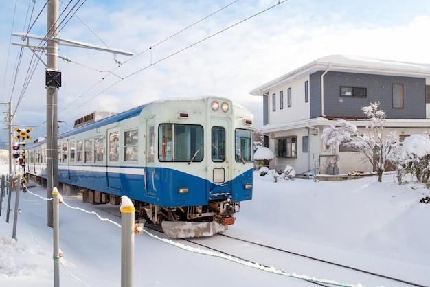 Trein die zich op spoorwegspoor beweegt voor lokale trein met witte sneeuwdaling van wintertijd, japan