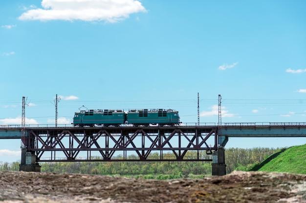 Trein gaat over de spoorbrug tegen de groene natuur. prachtig zomers landschap