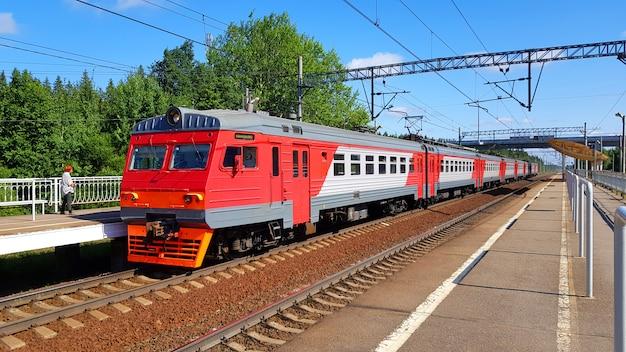 Trein in de voorsteden komt bij station in de zomer op zonnige dag aan. spoorwegplatform met trein onderweg.