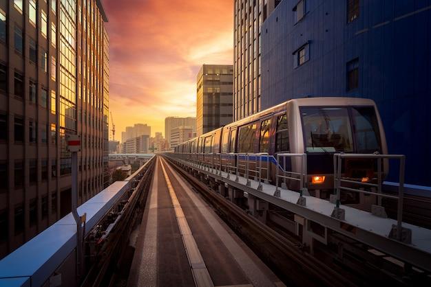 Trein in stad in tokyo met zonsondergangachtergrond