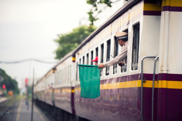 Treinfunctionarissen signaleren groene vlaggen voor treinen om mensen van het treinstation naar de hoofdstad te vervoeren