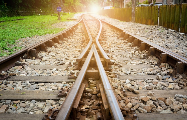 Treinsporen op grind, twee spoorbanen samenvoegen met zonsondergang achtergrond