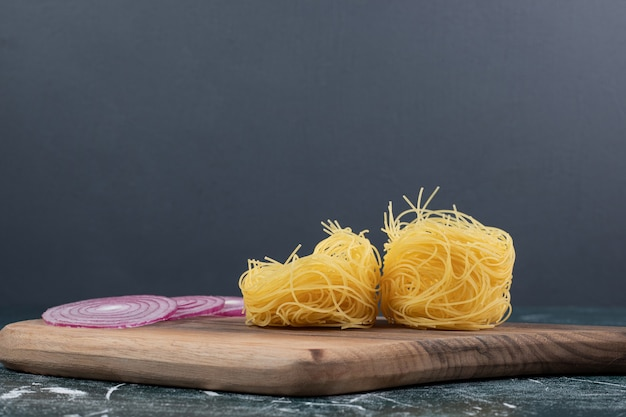 Trek ongekookte ronde macaroni met plakjes ui op een houten bord. hoge kwaliteit foto