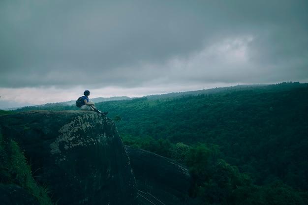 Treker op bergtop met grote groene bosachtergrond