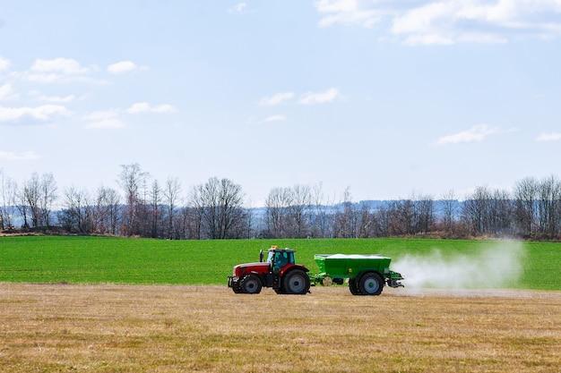 Trekker die kunstmest op grasgebied uitspreidt. landbouw werk.