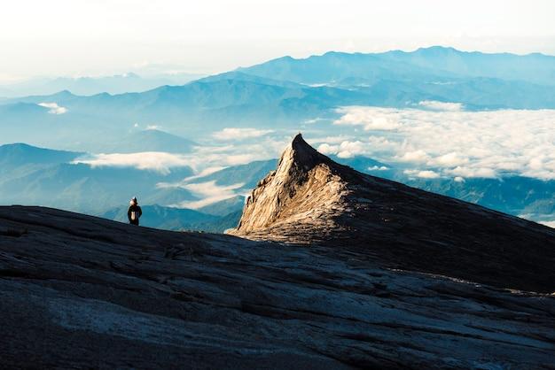Trekker die zich op kinabalu-berg met zuidenpiek en bergketen bevindt