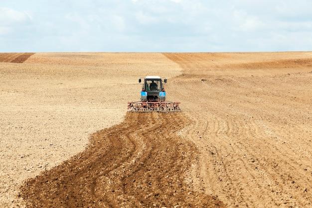 Trekker in het veld een oude tractor die het veld ploegt voordat de lente de hemel wordt gezaaid