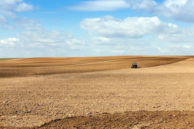 Trekker in het veld een trekker die een veld ploegt dat zich tijdens het planten in het land bevindt