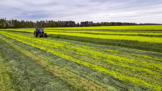 Trekker maaien groen veld