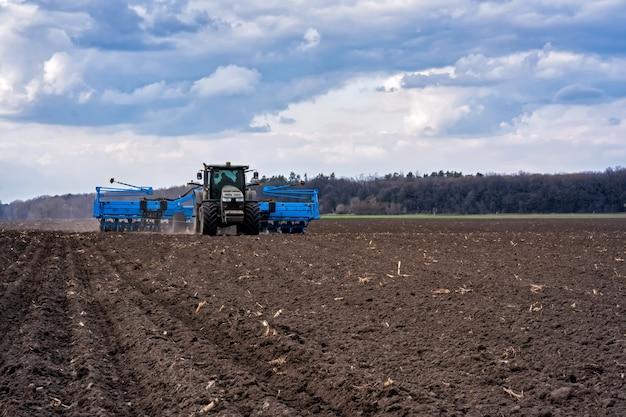 Trekker met aggregaat die de grond bewerkt