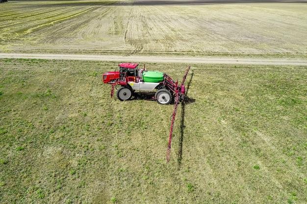 Trekker met hoge bodemvrijheid voor het besproeien van planten in de velden.