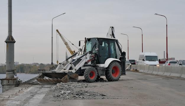 Trekker of graafmachine repareert brug, verwijdert afval