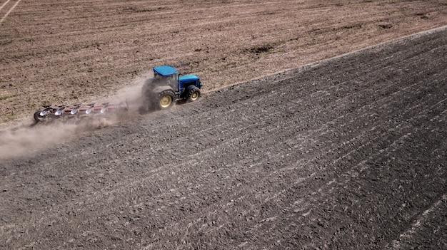 Trekker ploegen veld bovenaanzicht, luchtfotografie met drone