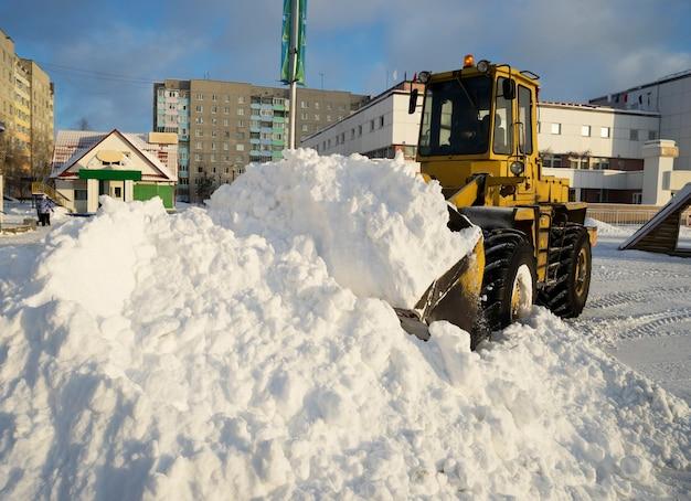 Trekker schop sneeuw in een stapel op straat.