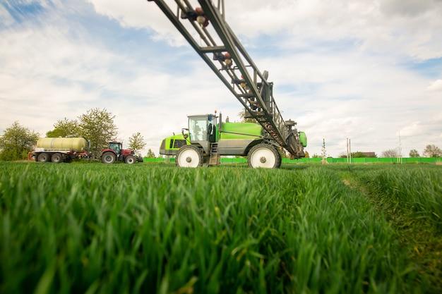 Trekker sproeien van pesticiden, bemesten op het groenteveld met sproeier in de lente, bemestingsconcept
