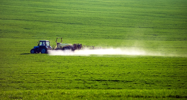 Trekker sproeien van pesticiden op veld met sproeier in de zomer