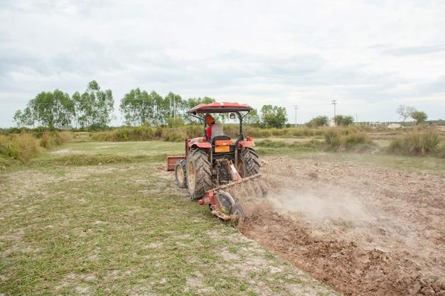 Trekker werken ploegt een veld op de boerderij om te planten